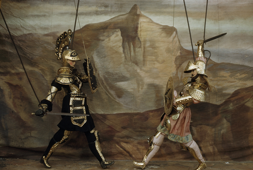 Marionettes dressed in armor enact sword fight.